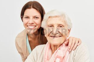 Enkelin zusammen mit glücklicher Seniorin