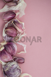 Broken red ripe garlic on a pastel pink background.