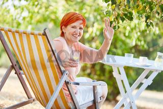 Frau mit einem Drink im Liegestuhl