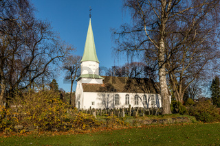 White wooden church seen from the side, trees, grass and blue sky in autumn, Kristiansand, Norway