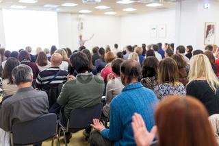 Woman giving interactive motivational speech at entrepreneurship workshop.