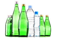 Composition with different sorts of bottles containing mineral water isolated on white