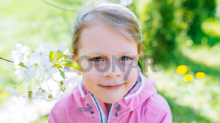 little laughing girl squinting eyes on a spring background