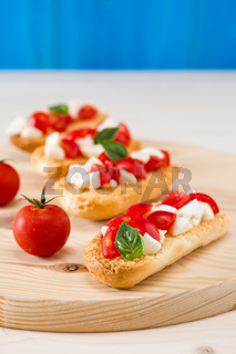 Italian crostini with mozzarella, cherry tomatoes and basil over a chopping board