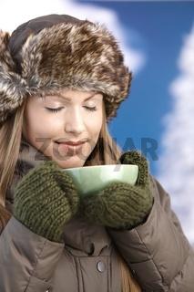 Young female dressed warm enjoying hot tea