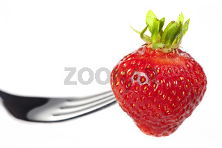 single strawberry on a fork isolated on white