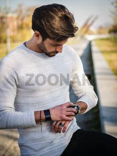 Handsome man outdoor using smartwatch