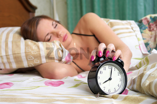 Young sleeping female turns alarm clock off  (woman out of focus)