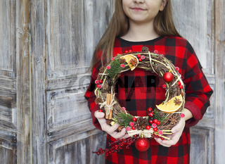 Christmas wreath in young womans hands