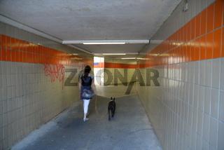 Frau und Hund in Unterführung