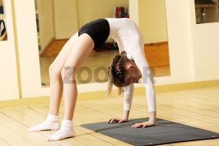 Little gymnast girl making bridge stand