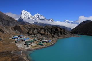 Turquoise Gokyo lake, village and mount Cholatse