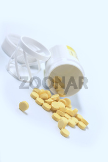 Heap of yellow tablets with a jar in blue light
