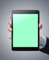 Male hand holding a mockup tablet on colored background