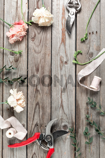 The florist work table with tools on gray wooden background. copy space