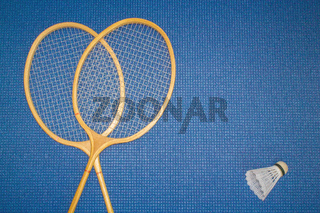Blue background. Mat for sport, yoga and meditation. Two badminton rackets and shuttlecock.