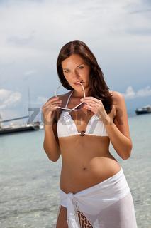 Brown hair fashion model in bikini by the sea on the beach