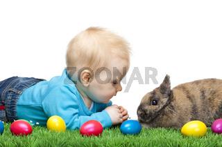 Baby liegt  in grüner Wiese mit Osterhasen und bunten Ostereiern