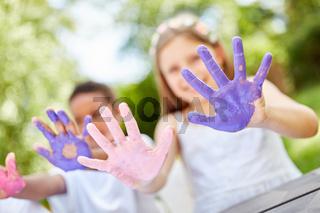 Kinder zeigen ihre bemalten Hände