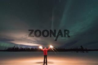Mann mit brennenden Wunderkerzen und Nordlicht (Aurora borealis), Lappland