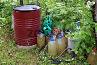Barrels, canisters and watering cans with water