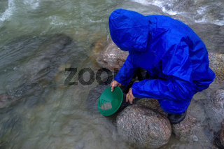 man, prospector panning gold in a river with sluice box on  rainy day