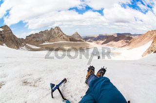 Tourists rest in the mountains on the glacier. First-person view. Sayram, Kazakhstan.