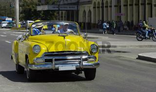 Amerikanischer gelber Cabriolet Oldtimer fährt in der Altstadt von Havanna Kuba