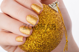 Beautiful well-groomed golden nails close up.