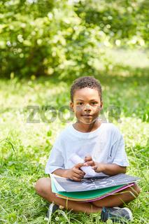 Junge in der Vorschule malt mit Kreide