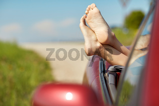 feet of young woman in convertible car at summer