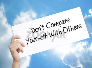 Don't Compare Yourself With Others Sign on white paper. Man Hand Holding Paper with text. Isolated on sky background