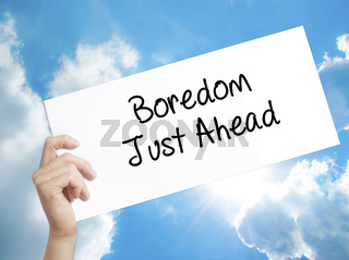 Boredom Just Ahead Sign on white paper. Man Hand Holding Paper with text. Isolated on sky background
