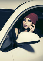 Young fashion woman calling on cell phone driving a car
