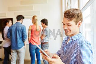 Junger Mann arbeitet mit Tablet Computer
