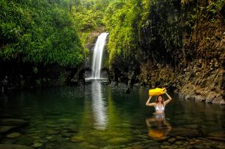 Young woman walking through lagoon with a dry bag at Wainibau Waterfall on Taveuni Island, Fiji