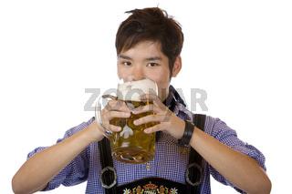 Chinese mit bayerischer Tracht trinkt aus Oktoberfest Maßkrug