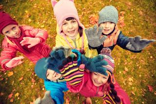 happy children waving hands in autumn park
