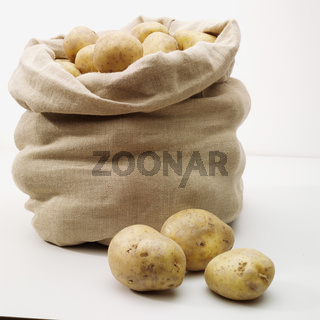 overflowing bag of potatos on whit