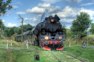 Old retro steam train passing through polish countryside