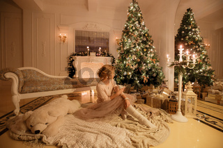 Christmas evening. Young beautiful blonde woman with cup of coffee sitting in classic apartments a white fireplace, decorated tree.