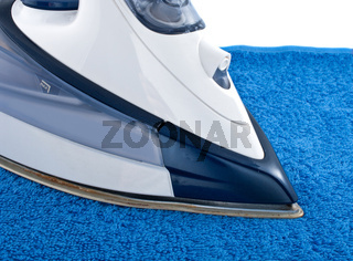 Electric iron on blue towel