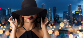 beautiful woman in black hat over singapore city