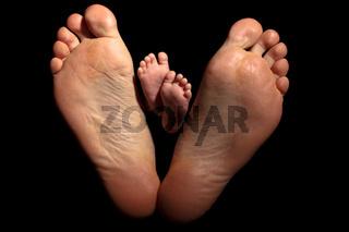 Babyfüße auf Vaters Füßen