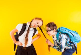 The cute little schoolboy pulls the schoolgirl's braid