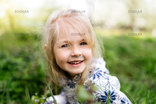 Little smiling girl with spring flowers on green lawn in the garden