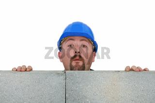 Builder peering over wall