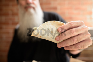 Hand of mature man with long gray beard holding taco