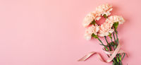 Bouquet of pink carnations. Design concept of holiday greeting with carnation bouquet on pink table background