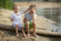 Two brothers, the elder and the younger, are playing by the river. Children on the sandy shore talk and indulge.